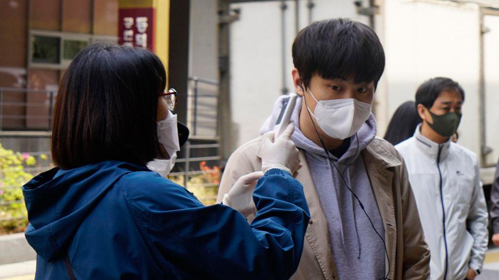 Una mujer chequea la temperatura de un hombre en Corea del Sur