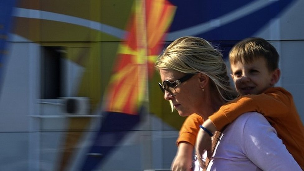 A woman carrying her son on her back walks in front of North Macedonian and EU flags in Skopje, North Macedonia, 18 October 2019