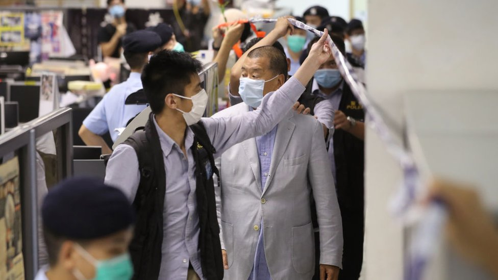Police lead Hong Kong media tycoon Jimmy Lai through his Apple Daily headquarters after a sweeping raid and arrests on August 10 2020