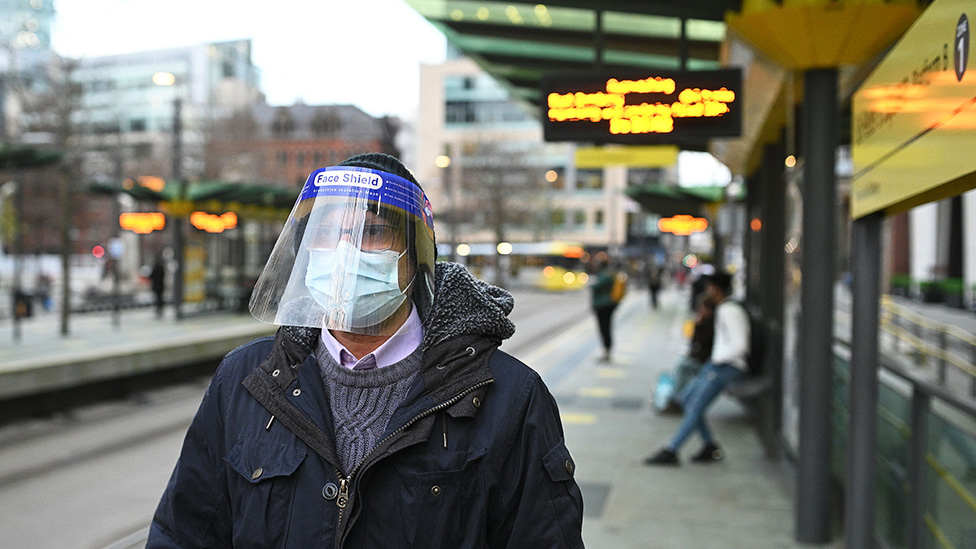 A person wearing a face covering and a full-face visor due to the Covid-19 pandemic, waits to board a tram in Manchester, northwest England - 26 November 2020