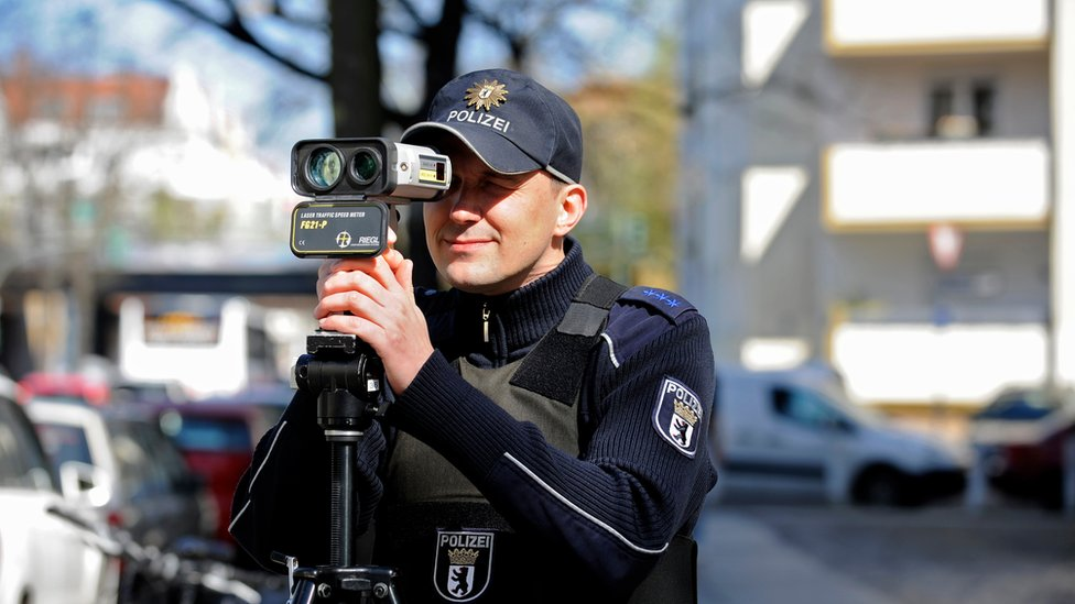 A German police officer holds a portable laser speed trap to his eye in this 2016 file photo
