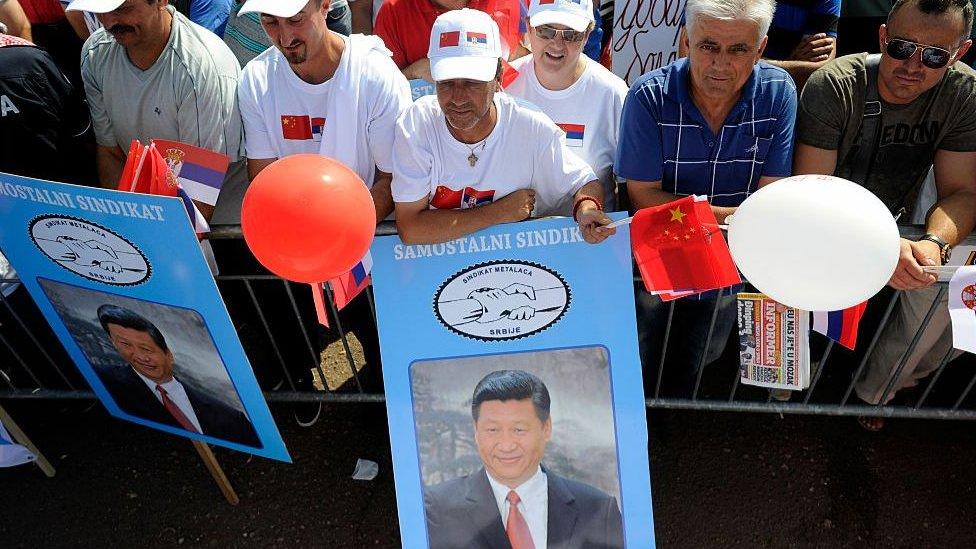 Serbios muestran banderas chinas y carteles con el rostro del presidente chino Xi Jinping.