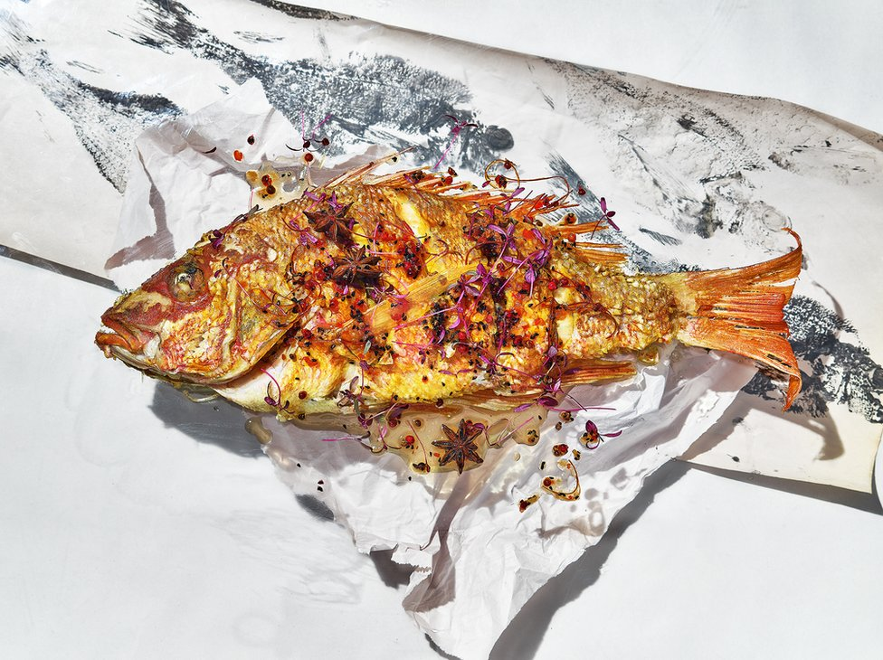 A cooked fish on paper with abstract fish prints on