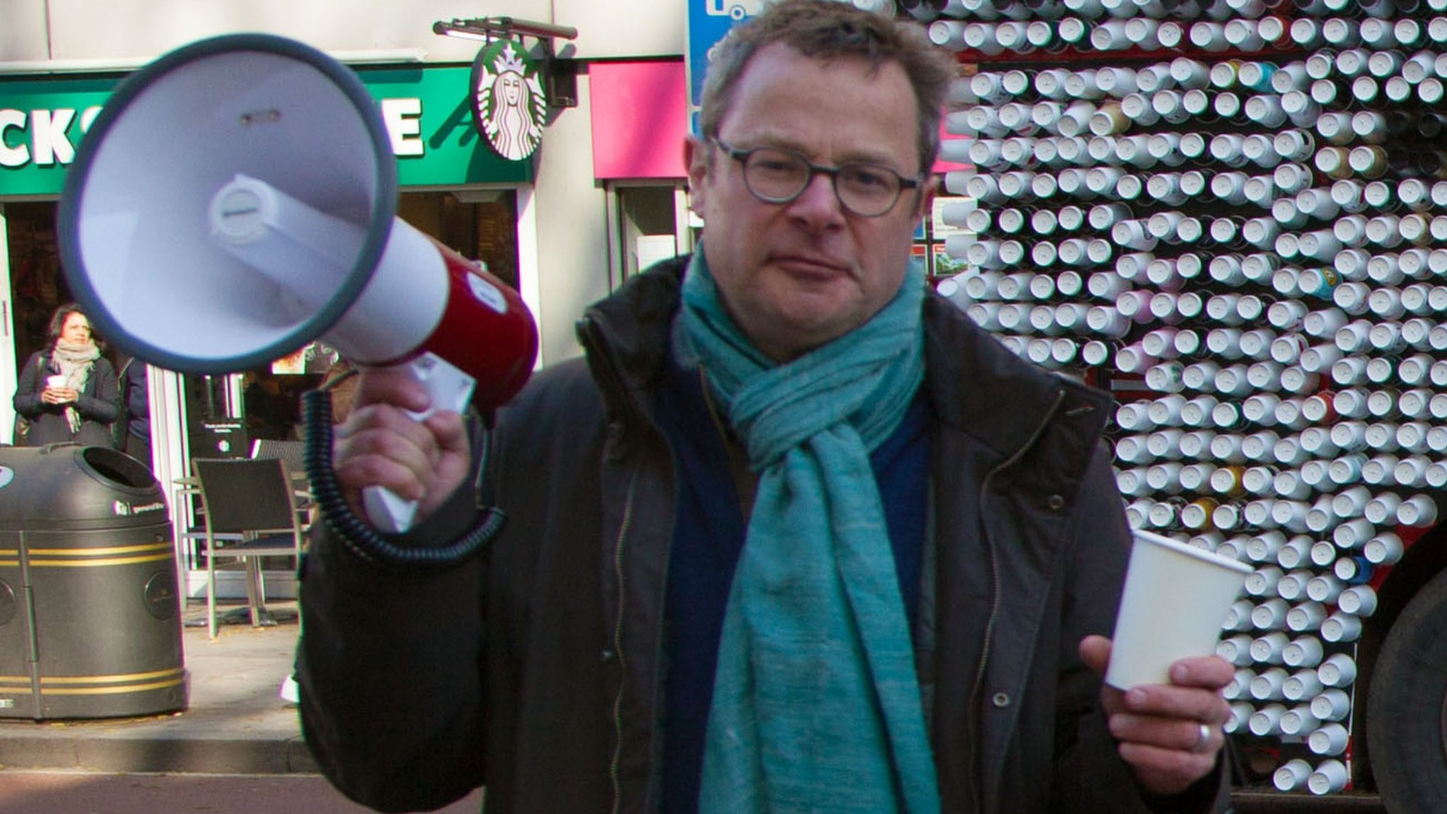 Hugh Fearnley-Whittingstall standing in front of a bus made of cups
