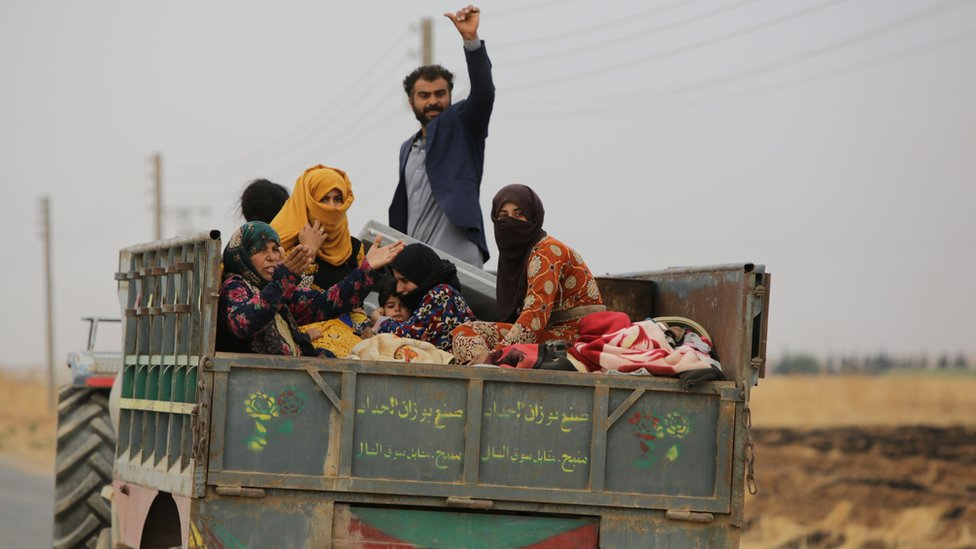 Syrian civilians ride in the back of a trailer as they flee the countryside around Tal Abyad, northern Syria (24 October 2019)