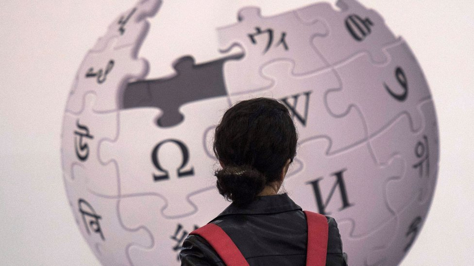 A woman stands with her back to the camera, in front of an enormous Wikipedia logo of various jigsaw pieces with different symbols forming a globe