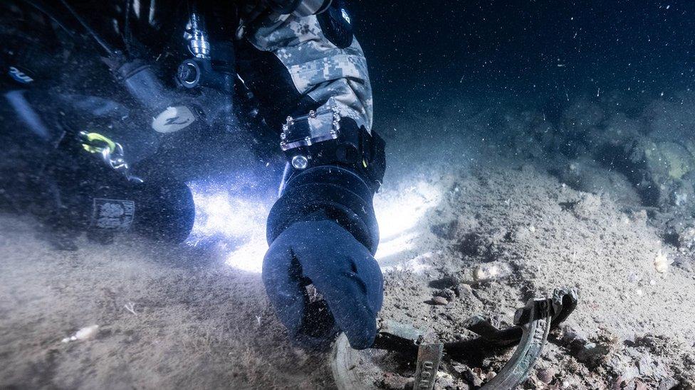 Un buzo apunta a una marca de la marina estadounidense en los restos de USS Eagle PE-56.