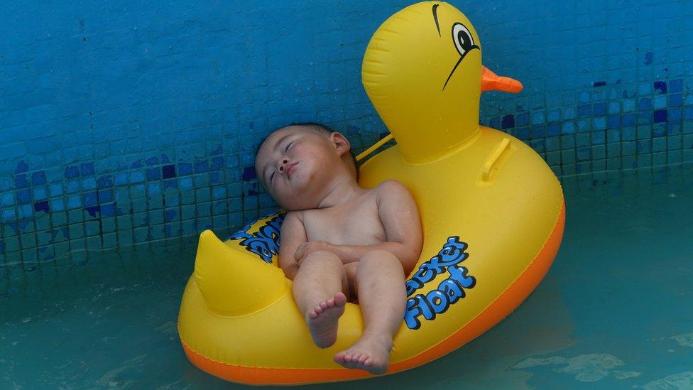 Çin'de 2014'teki sıcak hava dalgası sırasında havuzdaki dalgalarla sallanan bir şişme ördeğin üzerinde uyuyakalmış bir bebek