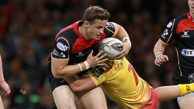 Hallam Amos of Newport Gwent Dragons is tackled by the Scarlets' James Davies on Judgement Day 2015