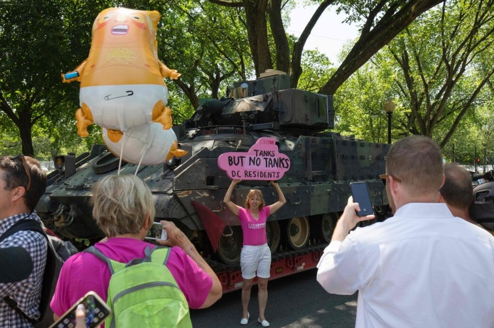 A protester stands next to a tank