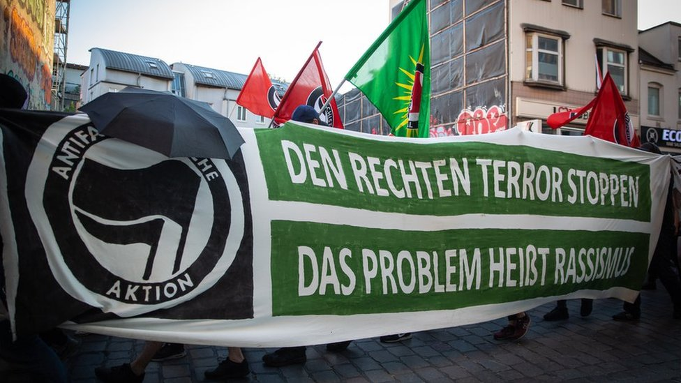 """Flags are raised above an anti-fascist demonstration, behind a banner reading, in German, """"Stop the far-right terror, the problem is called racism"""""""