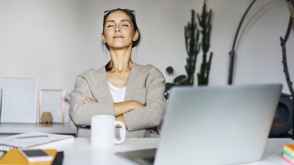Una mujer respira en un recre de trabajo en su casa.