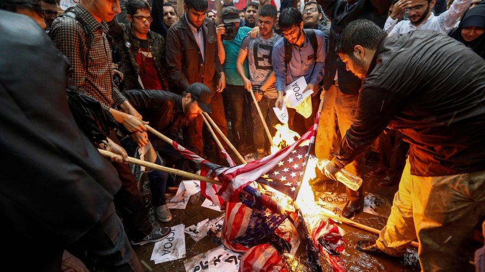 متظاهرون إيرانيون يحرقون العلم الأمريكي في طهران