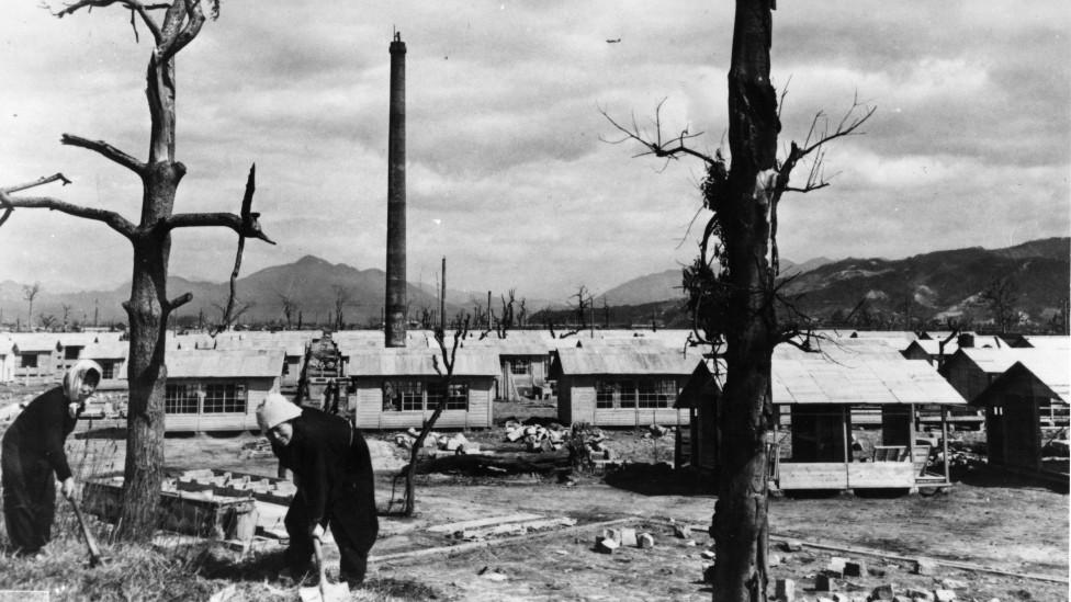 Dos mujeres construyen casas precarias de emergencia tras la bomba atómica. Junto a ellas se ven los troncos carbonizados de dos árboles.