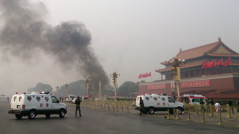 Police cars block off the roads leading into Tiananmen Square as smoke rises into the air after a vehicle crashed in front of Tiananmen Gate in Beijing on 28 October 2013.