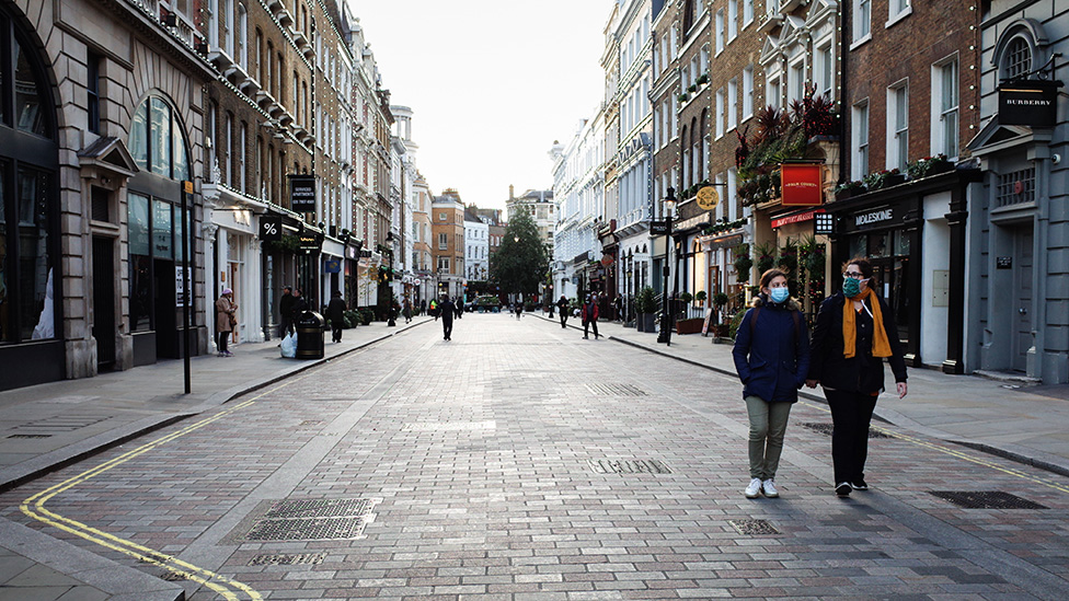 People wearing masks walk through deserted Covent Garden, central London