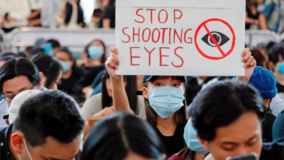 """Cartel que dice """"Dejen de dispararnos a los ojos"""""""