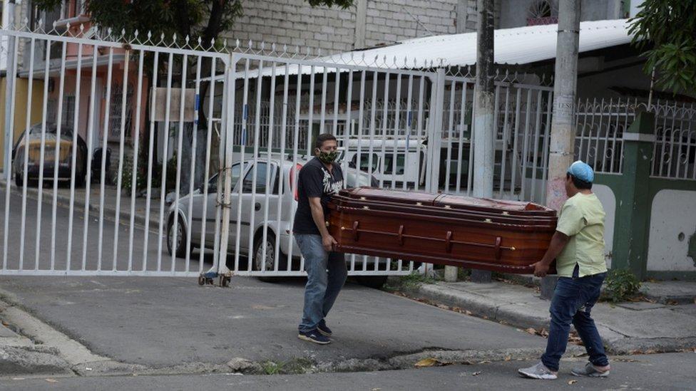 Dos hombres llevan un ataúd por las calles de Guayaquil.