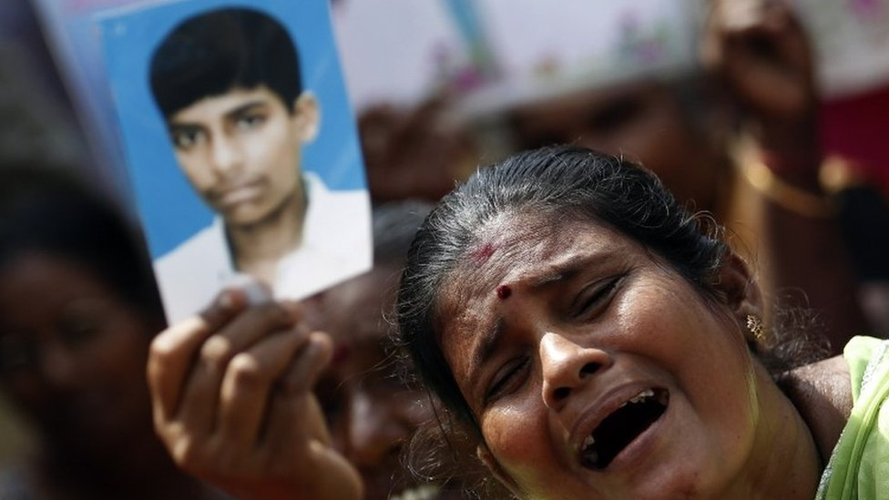 A Tamil woman holds up an image of her disappeared family member during the war against Liberation Tigers of Tamil Eelam (LTTE), at a protest in Jaffna (27 August 2013)