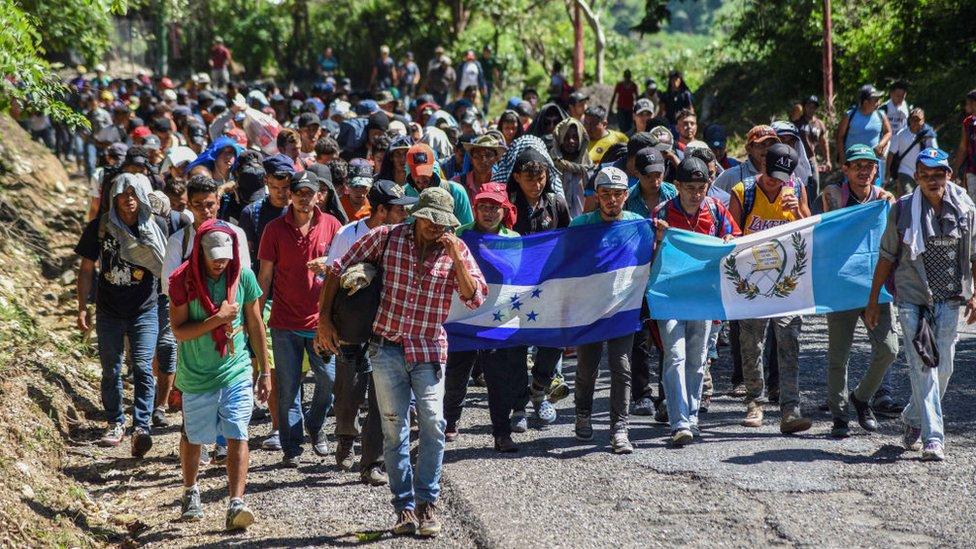 Migrantes marchan con banderas al frente