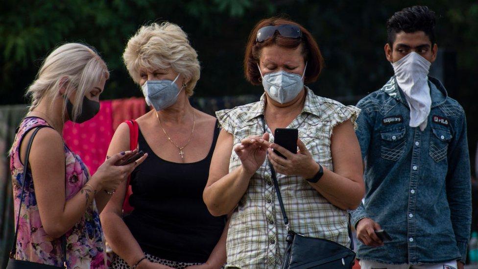 Un grupo de personas con mascarillas mirando sus celulares