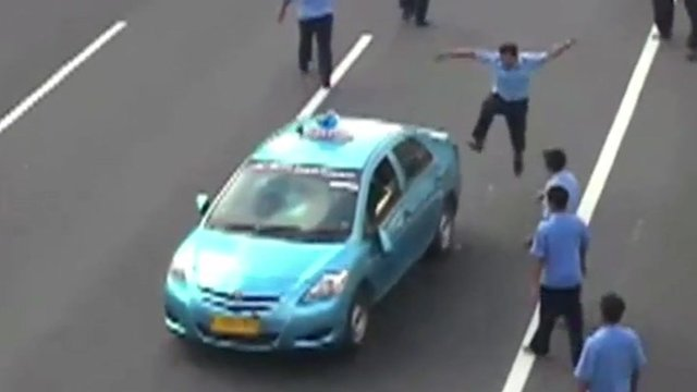 A striking Indonesian taxi driver kicking a taxi