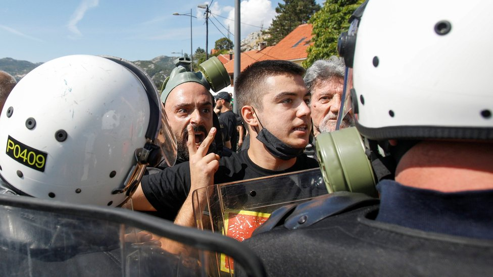 Demonstrators argue with police during a protest against enthronement of Bishop Joanikije in Cetinje