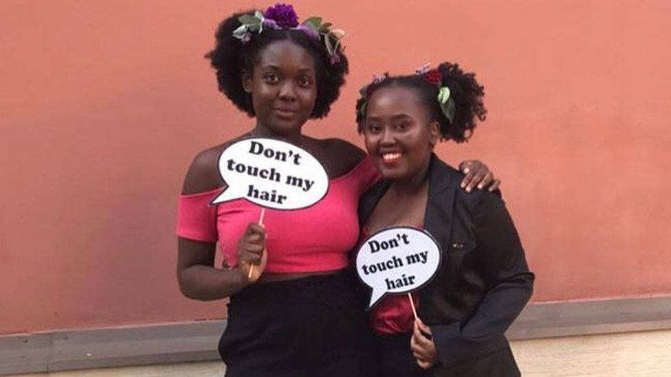 "Two women with ""don't touch my hair"" signs"