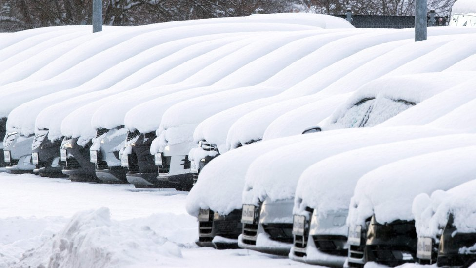 A thick blanket of snow lies on cars at a used car dealer in Rehna, Germany