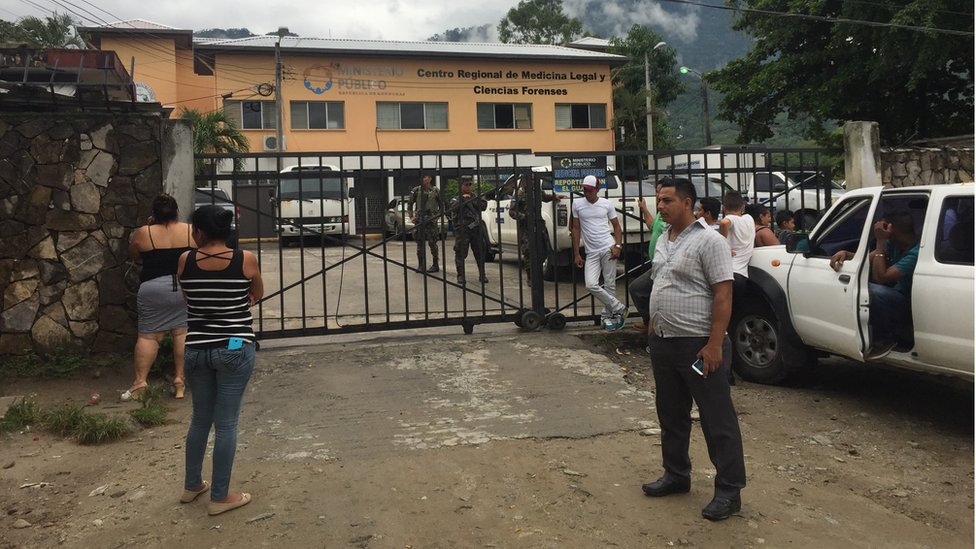 People stand outside a morgue guarded by military men in San Pedro Sula