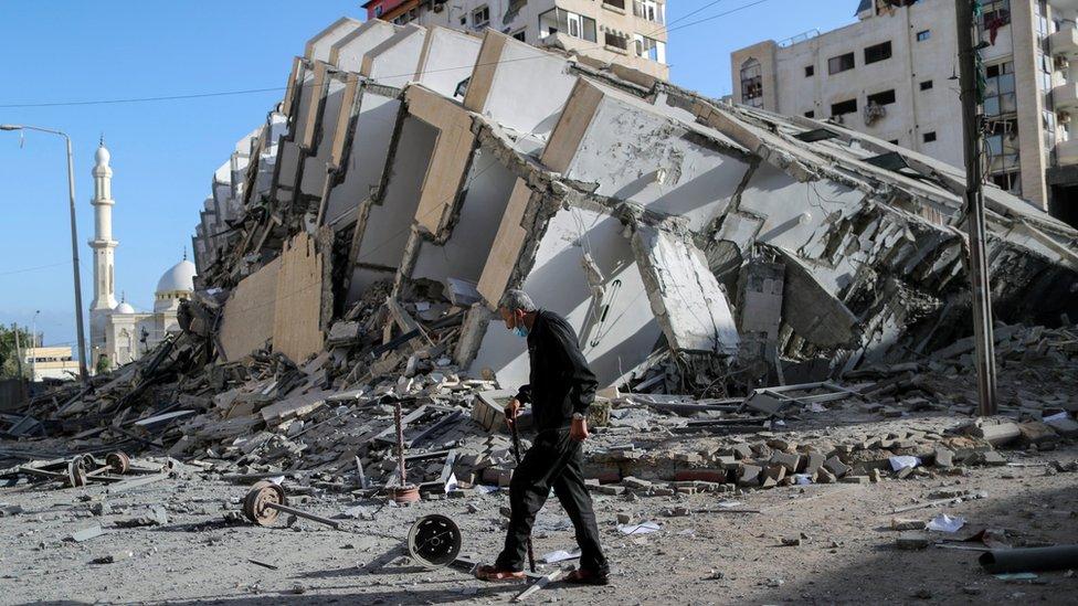 Un hombre palestino frente a una torre derribada por un ataque aéreo israelí en Gaza.