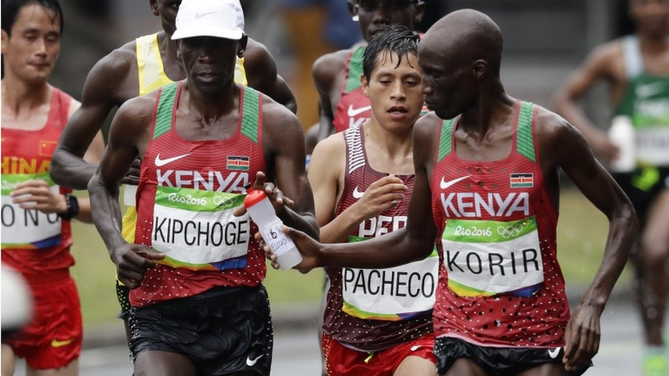 """Wesley Korir, of Kenya, right, hands a bottle of water to eventual winner Eliud Kipchoge, also of Kenya, in the men""""s marathon at the 2016 Summer Olympics in Rio de Janeiro, Brazil, Sunday, Aug. 21, 2016."""