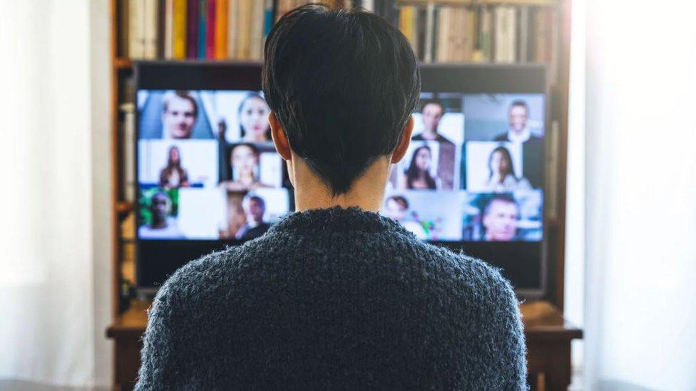 Un joven de espaldas mirando un televisor con Zoom.
