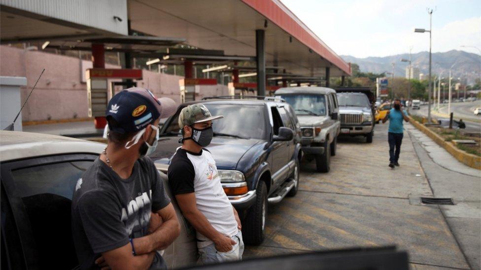 أشخاص يرتدون أقنعة وجه يقفون الى جانب مركباتهم في طابور في محطة وقود أثناء الحجر الصحي المفروض على الصعيد الوطني استجابة لانتشار فيروس كورونا في كاراكاس، فنزويلا 30 مارس/آذار 2020