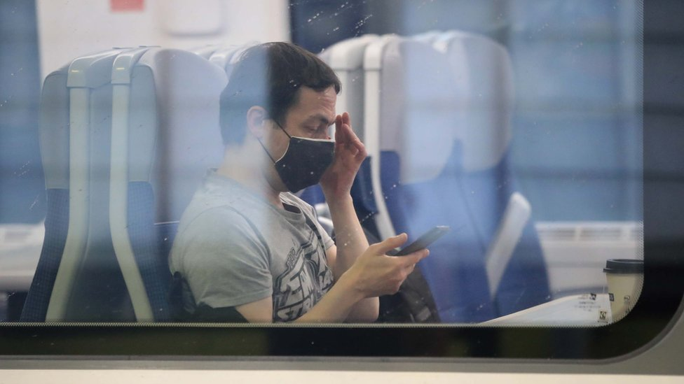 A man wearing a mask on a train