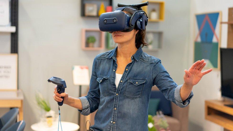 Una mujer usando un visor de realidad virtual.