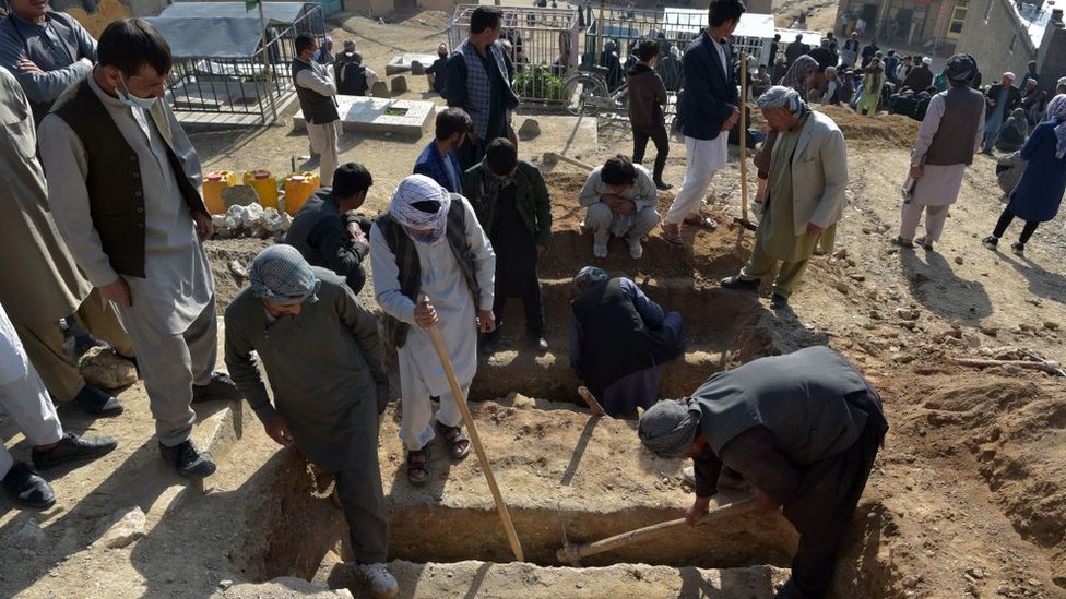 People bury victims of a series of blasts near a school in Kabul which killed more than 50 people