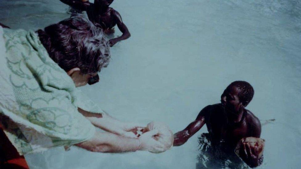 Pandit daje kokosov orah Sentinelcima prilikom ekspedicije 1991. godine