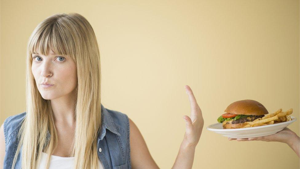 Mujer rechazando una hamburguesa.