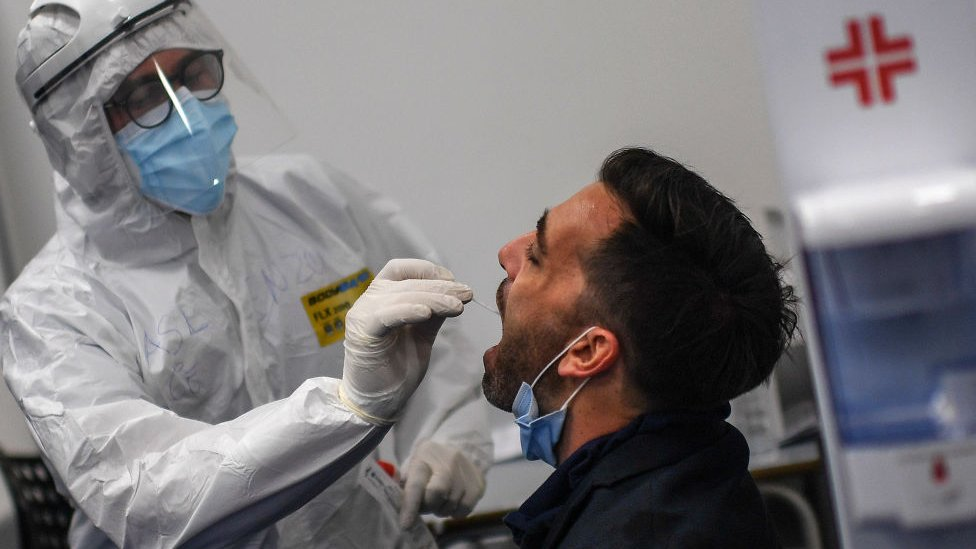 Trabajador de la salud hace la prueba de coronavirus a un viajero en el aeropuerto de Nápoles.