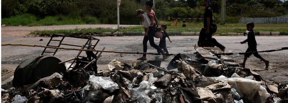 Venezuelans walk past belongings and tents burned by civilians at the Pacaraima border control, Roraima State, Brazil August 19, 2018.