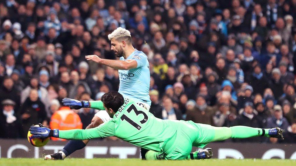 لاعب مانشستر سيتي سيرجيو أغويرو في تسديدة قوية إلى مرمى أليسون بيكر