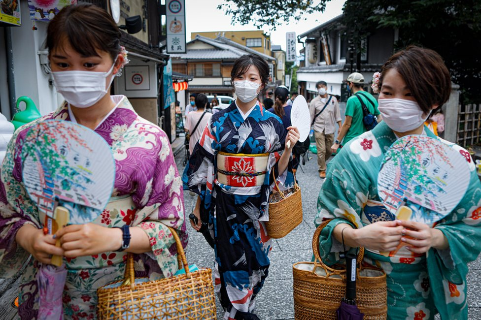 Women wearing protective face masks walk near Kiyomizudera temple in Kyoto, Japan.
