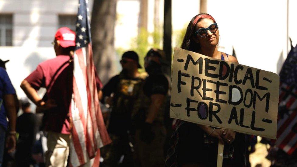 """Una mujer en una protesta antivacuna con un cartel que lee """"Libertad médica para todos"""""""