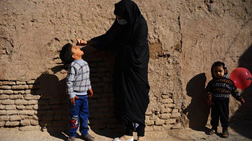 Una mujer vacuna un niño
