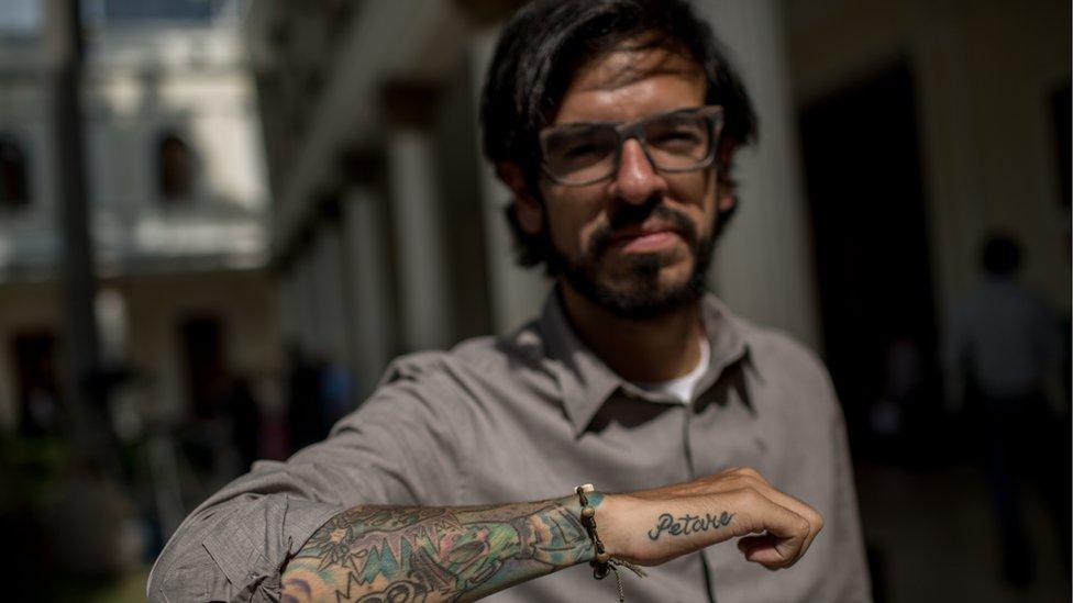 "Lawmaker Miguel Pizarro shows of his tattoo reading ""Petare"""