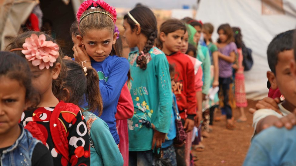 Displaced Syrian children stand in line at a makeshift school at a camp in Atmeh, Idlib province (1 October 2018)