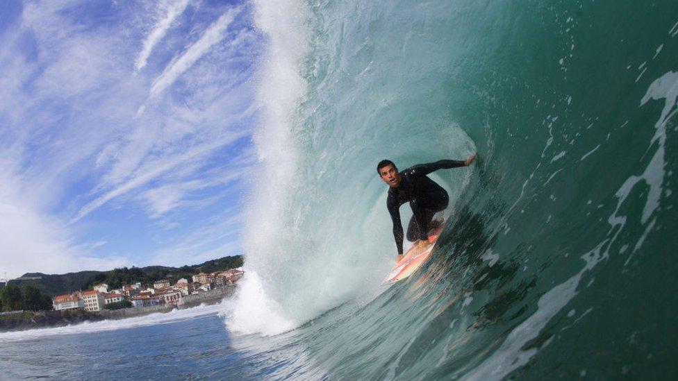 Un hombre hace surf en la playa de la ciudad costera de Mundaka en, el País Vasco, España