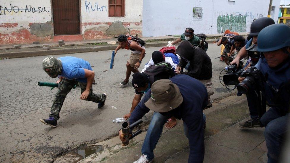 Grupo de manifestantes portando armas caseras.