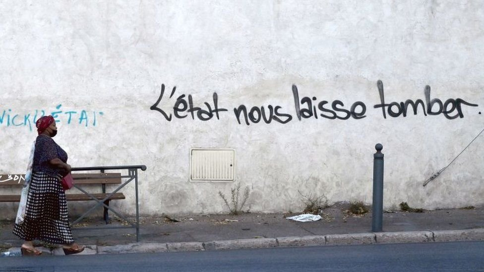 """A woman walks in a street in """"Les Marronniers"""" neighbourhood as a handwriting reads 'State lets us down' on the wall, on August 30, 2021"""